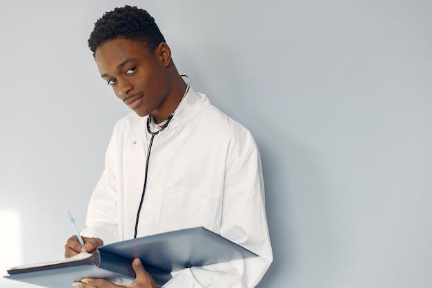Medico nero in uniforme bianca con uno stetoscopio Foto Gratuite