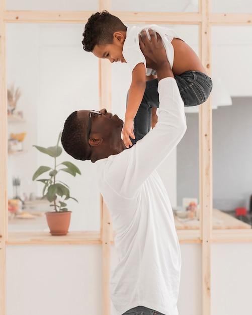 Medium shot padre giocando con suo figlio in casa Foto Gratuite