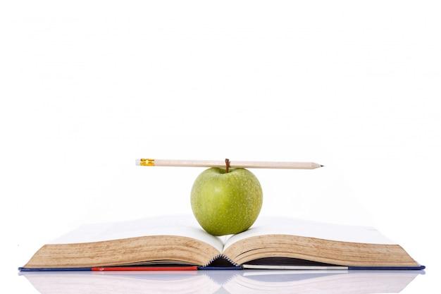 Mela e matita verdi sul libro. Foto Premium