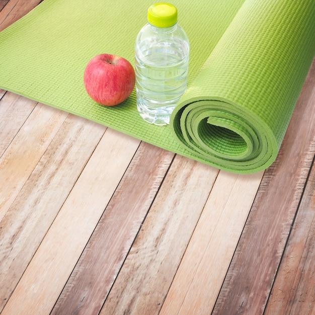 Mela rossa, bottiglia d'acqua e tappetino yoga Foto Premium