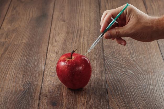 Mela rossa che inietta un ago o una siringa e pesticidi chimici su un fondo di legno Foto Premium