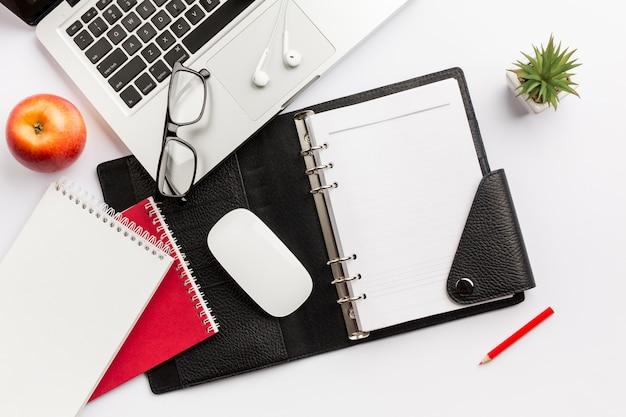 Mela rossa, diario, mouse, occhiali, auricolari, matita e laptop sulla scrivania bianca Foto Gratuite