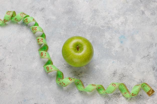 Mela verde fresca, nastro di misura e bottiglia di acqua dolce su calcestruzzo grigio Foto Gratuite