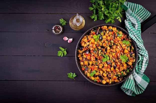 Melanzane stufate vegetariane, peperoni, cipolle, aglio e pomodori alle erbe Foto Premium