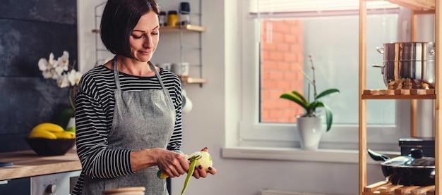 Mele della sbucciatura della donna nella cucina Foto Premium