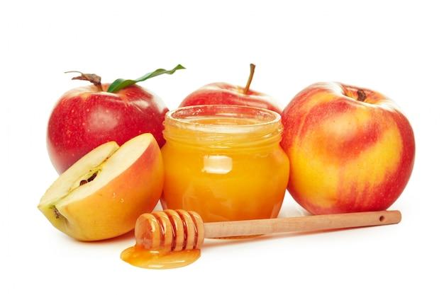 Mele e barattolo del miele per la festa ebrea del nuovo anno isolata su bianco Foto Premium