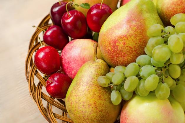 Mele fresche, pere, uva e prugne in un piatto di legno intrecciato Foto Premium