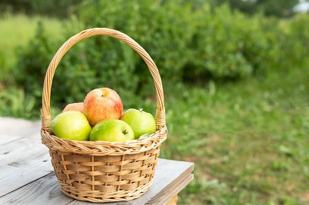 Mele verdi e rosse nel cesto di vimini sul tavolo di legno erba verde nel giardino tempo di raccolta Foto Premium