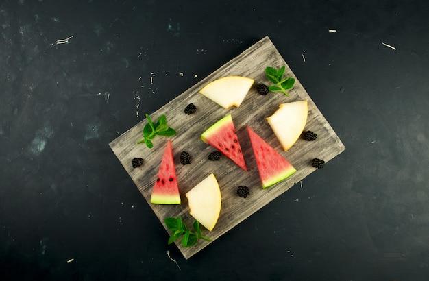 Melone, anguria, more e menta su un tavolo di legno Foto Premium