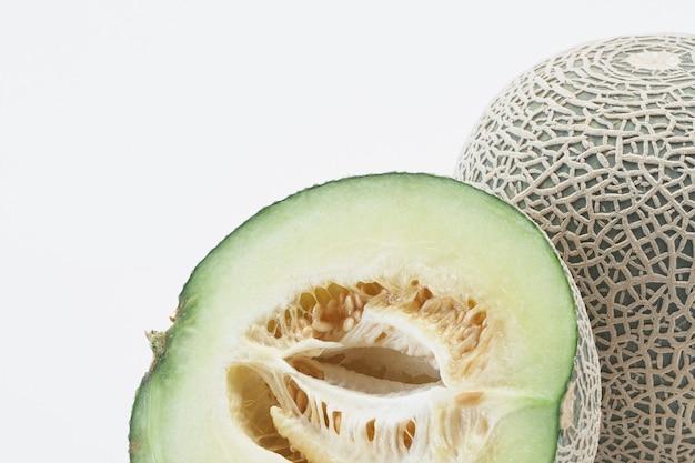 Melone fresco del cantalupo di hami con le fette isolate su fondo bianco. Foto Premium