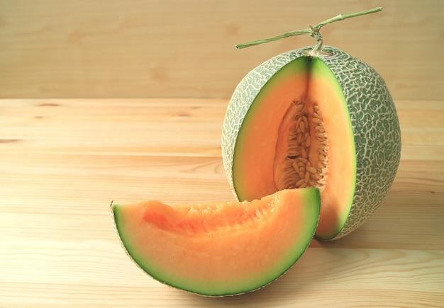Melone maturo sugoso di colore arancio luminoso del cantalupo affettato da intera frutta sulla tavola di legno Foto Premium