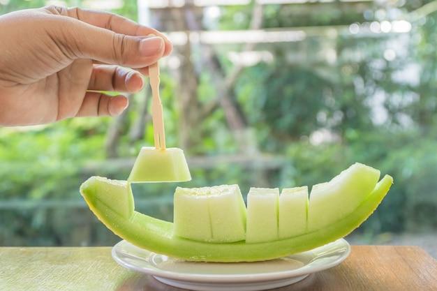 Melone tagliato a pezzi e con un bastoncino.melone mise un piatto su un tavolo di legno. Foto Premium