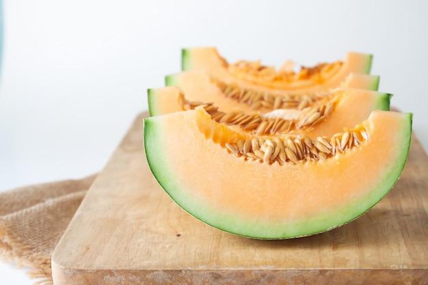 Meloni giapponesi affettati sul tagliere di legno su fondo bianco Foto Premium