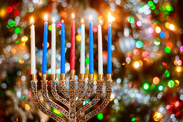 Menorah con candele accese per hanukkah su sfondo scintillante con luci sfocati. Foto Premium