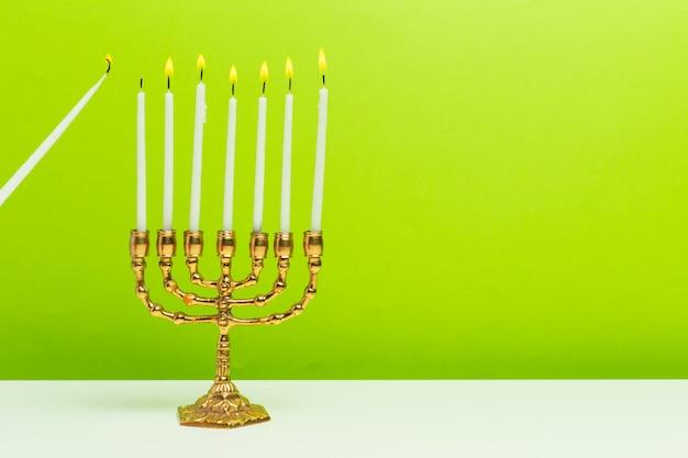 Menorah di bronzo hanukkah con candele accese Foto Premium