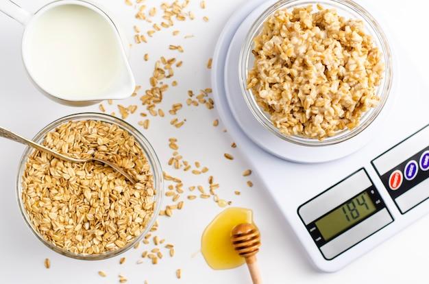 Menu nutrizionale adeguato per la colazione con porridge di farina d'avena su bilance da cucina digitali, latte e miele Foto Premium