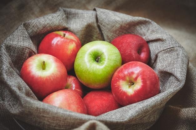Merce nel carrello rossa della mela e della mela verde con struttura del fondo della tela di sacco Foto Premium