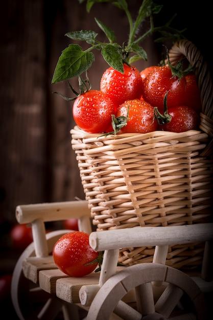 Merce nel carrello rossa succosa dei pomodori sulla tavola di legno, primo piano Foto Premium