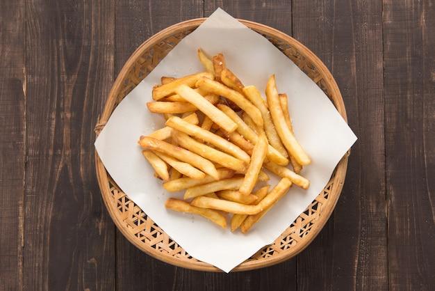 Merce nel carrello tradizionale delle patate fritte su fondo di legno Foto Premium