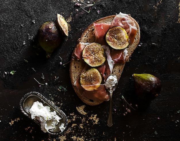 Merenda estiva con prosciutto di parma, fichi e formaggio fresco su pane di segale Foto Premium