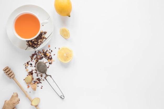 Merlo acquaiolo del miele; filtro; erbe aromatiche; limone; zenzero e tazza di tè allo zenzero su sfondo bianco Foto Gratuite