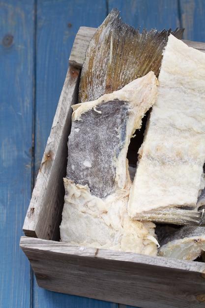 Merluzzo salato in scatola di legno su fondo di legno blu Foto Premium