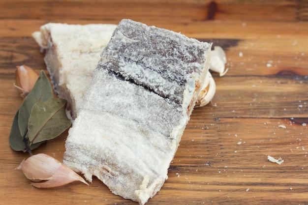 Merluzzo secco salato su superficie di legno Foto Premium