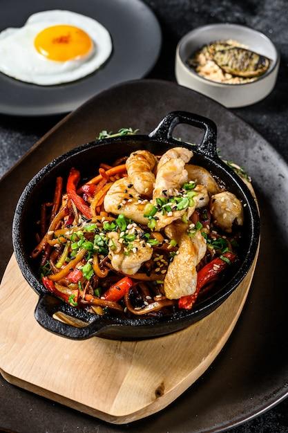 Mescolare gli spaghetti fritti con verdure, pollo. wok noodles. sfondo nero. vista dall'alto Foto Premium