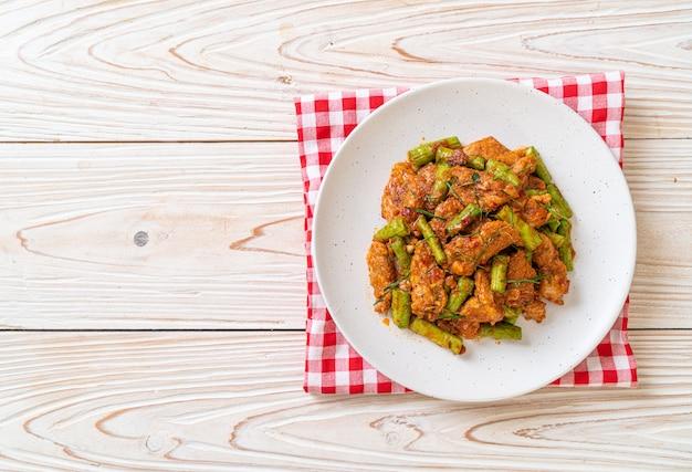 Mescolare la carne di maiale fritta e pasta di curry rossa con fagiolo, stile asiatico Foto Premium