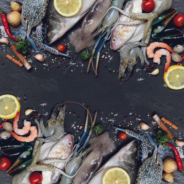 Mescolare pesce frutti di mare crudi freschi con erbe e spezie limone su scuro Foto Premium