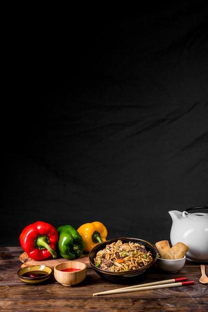 Mescolare tagliatelle fritte con verdure e pollo con peperoni; salse e involtini primavera sulla scrivania su sfondo nero Foto Gratuite