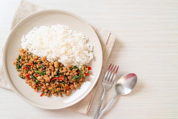 Mescoli il basilico tailandese fritto con carne di maiale tritata su riso sormontato Foto Premium
