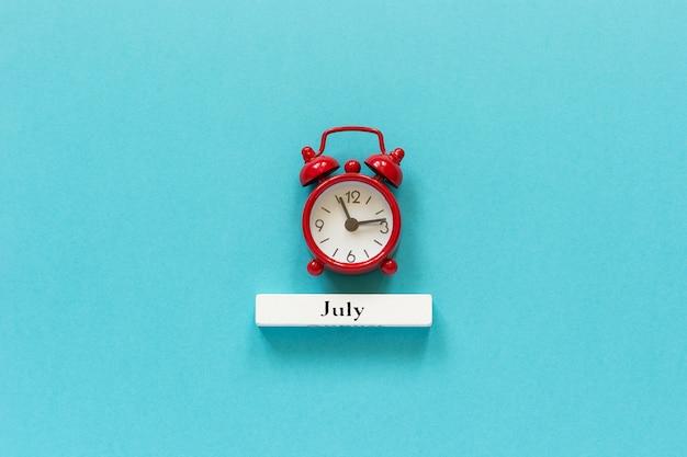 Mese di luglio del calendario di legno luglio e sveglia rossa sul fondo della carta blu. Foto Premium
