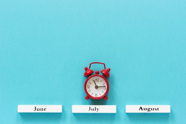 Mesi estivi in legno del calendario e sveglia rossa sopra luglio su fondo blu. Foto Premium