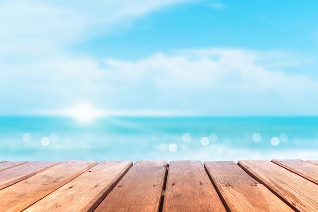 Messa a fuoco selettiva del vecchio tavolo in legno con sfondo bellissimo spiaggia per visualizzare il tuo prodotto. Foto Premium