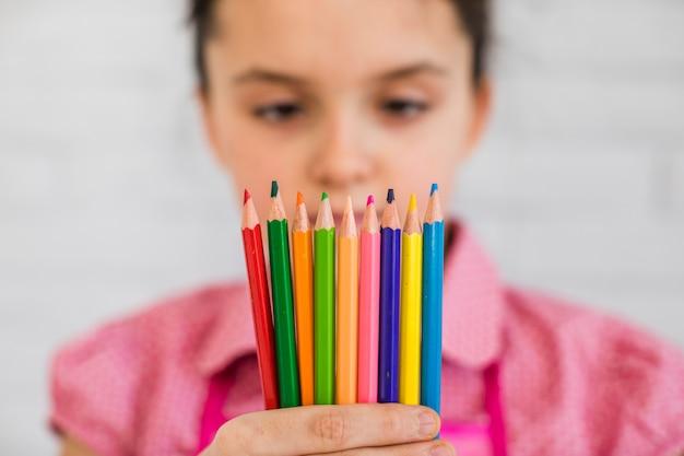 Messa a fuoco selettiva di una ragazza guardando matite colorate in mano Foto Gratuite