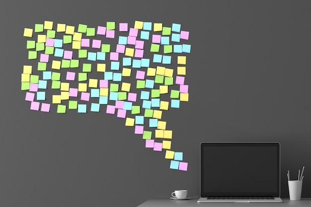 Messaggio dal messaggero dagli adesivi incollati sul muro con un laptop in piedi accanto Foto Premium