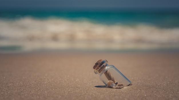 Messaggio in bottiglia sulla spiaggia di sabbia Foto Premium