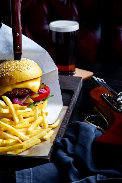 Mestiere l'hamburger e le patate fritte del manzo sulla tavola in ristorante con vetro di birra su oscurità. cornice per il pranzo moderna fast food Foto Premium