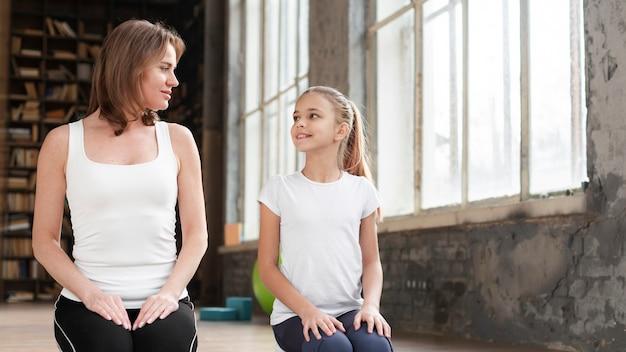 Metà colpo mamma e ragazza seduta sulla stuoia di yoga Foto Gratuite