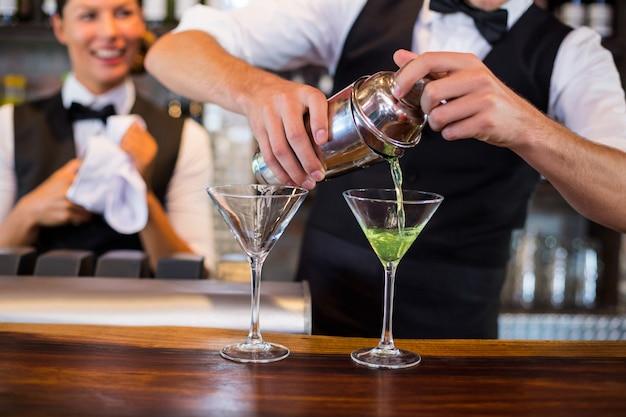Metà di sezione del barista che versa cocktail nei bicchieri Foto Premium
