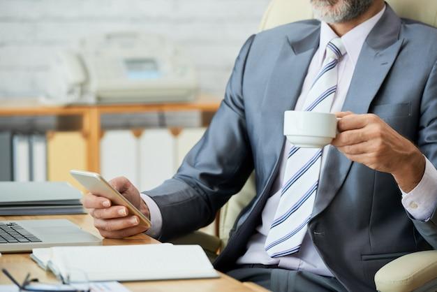 Metà di sezione dell'impiegato dall'aspetto professionale che beve caffè e naviga in rete su smartphone Foto Gratuite