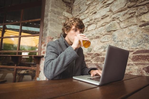 Metà di sezione dell'uomo che tiene vetro di birra e che per mezzo del computer portatile Foto Gratuite