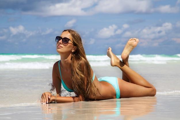 Metà di sezione della giovane donna in bikini blu che prende il sole sulla sabbia bianca. ragazza di moda che si abbronza sulla spiaggia tropicale Foto Premium