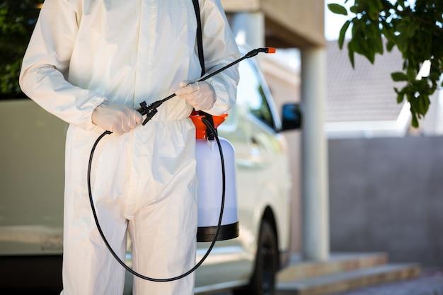 Metà di sezione di controllo dei parassiti uomo in piedi accanto a un furgone Foto Premium