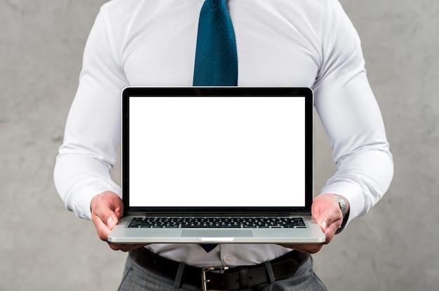 Metà di sezione di un computer portatile della tenuta dell'uomo con lo schermo bianco in bianco contro la parete grigia Foto Gratuite