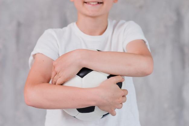 Metà di sezione di un ragazzo che abbraccia il pallone da calcio contro la palla concreta Foto Gratuite