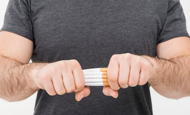 Metà di sezione di un uomo che rompe il pacco di sigarette con due mani Foto Gratuite