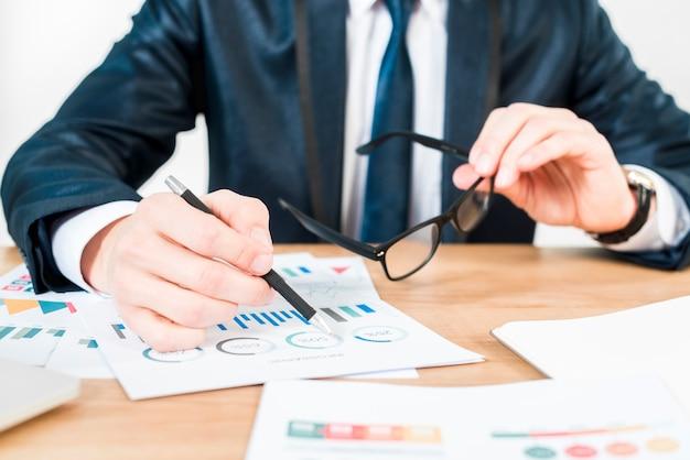 Metà di sezione di un uomo d'affari che giudica gli occhiali neri a disposizione che analizzano il grafico sulla tavola di legno Foto Gratuite