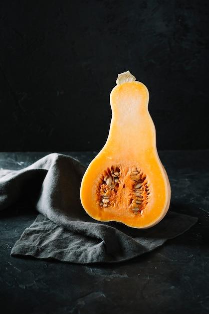Metà di zucca butternut organica cruda su fondo e panno neri Foto Gratuite